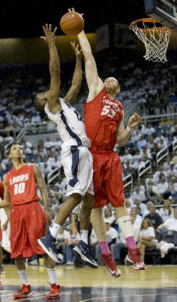 New Mexico's Alex Kirk blocks the shot of Nevada's Deonte Burton during the second half of an NCAA college basketball game Sunday, March 2, 2014, in Reno, Nev