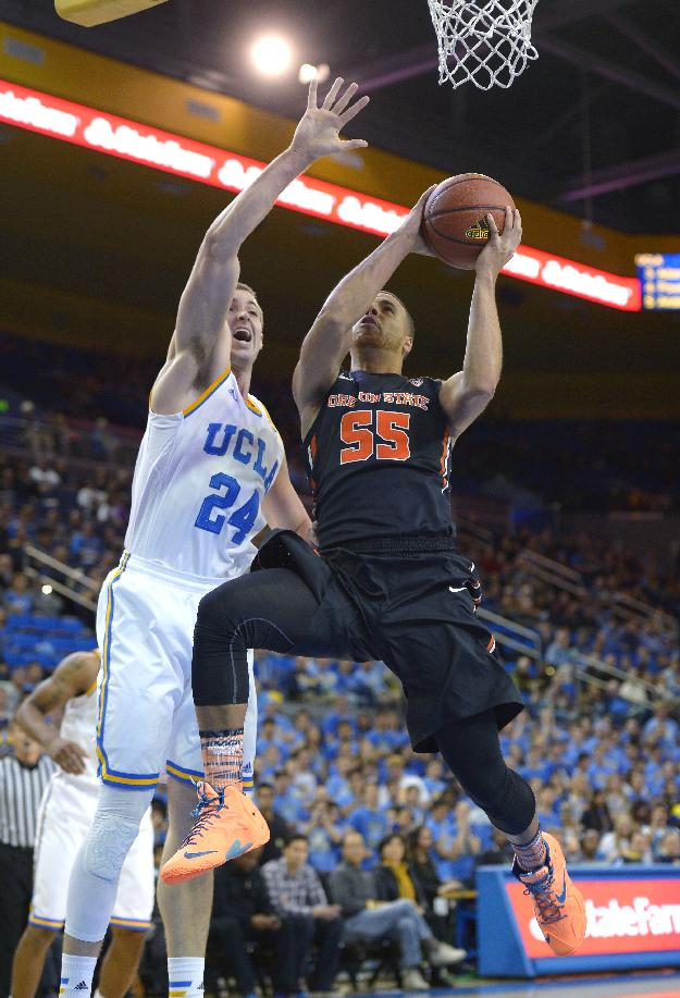 Oregon State guard Roberto Nelson, right, puts up a shot as UCLA forward Travis Wear defends during the first half of an NCAA college basketball game, Sunday, March 2, 2014, in Los Angeles