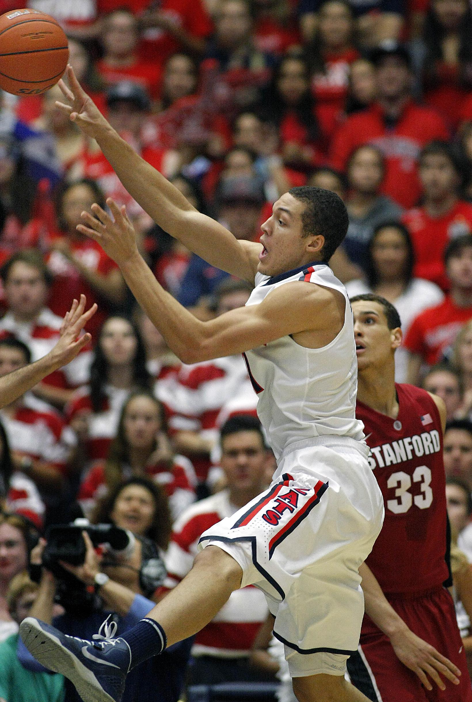 Arizona's Aaron Gordon, center, passes the ball in front of Stanford's Dwight Powell (33) in the first half of an NCAA college basketball game, Sunday, March 2, 2014  in Tucson, Ariz