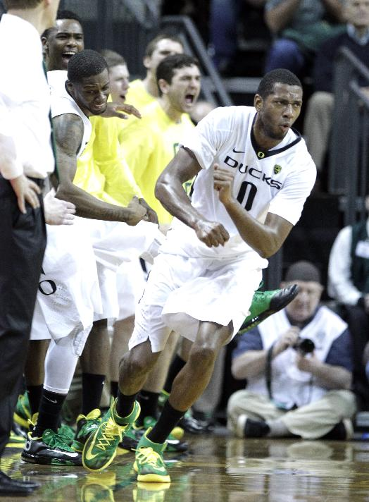 Oregon forward Mike Moser, right, celebrates sinking a three point shot in front of the Oregon bench during the second half of an NCAA college basketball game against Arizona State in Eugene, Ore., Tuesday, March 4, 2014.  Moser led Oregon with 22 points and 17 rebounds as they beat Arizona State 85-78