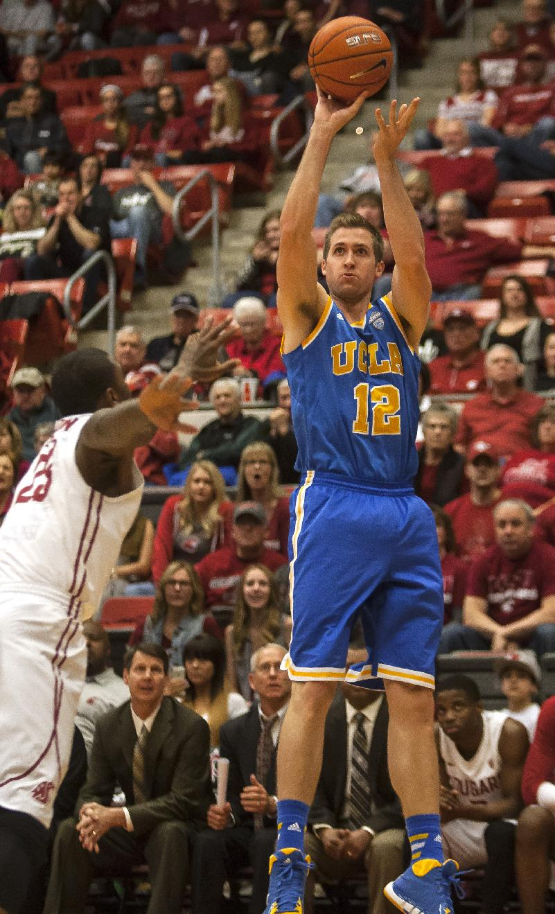 UCLA forward David Wear (12) releases a 3-point shot over Washington State forward D.J. Shelton (23) during the first half of an NCAA college basketball game Saturday, March 8, 2014, at Beasley Coliseum in Pullman, Wash