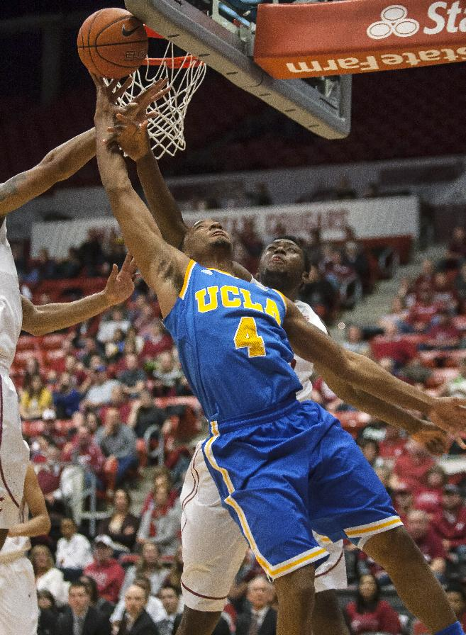 UCLA guard Norman Powell (4) shoots after getting past Washington State forward Junior Longrus, obscured, as center Jordan Railey, left, helps defend during the first half of an NCAA college basketball game Saturday, March 8, 2014, at Beasley Coliseum in Pullman, Wash