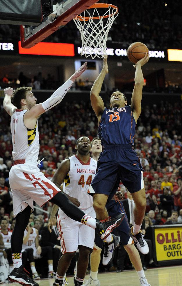 Virginia guard Malcolm Brogdon (15) goes to the basket against Maryland forward Evan Smotrycz during the first half of an NCAA college basketball game, Sunday, March 9, 2014, in College Park, Md. Also seen is Maryland center Shaquille Cleare (44)