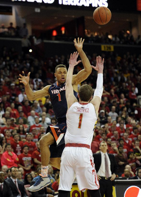 Virginia guard Justin Anderson, left, passes the ball against Maryland forward Evan Smotrycz (1) during the first half of an NCAA college basketball game, Sunday, March 9, 2014, in College Park, Md