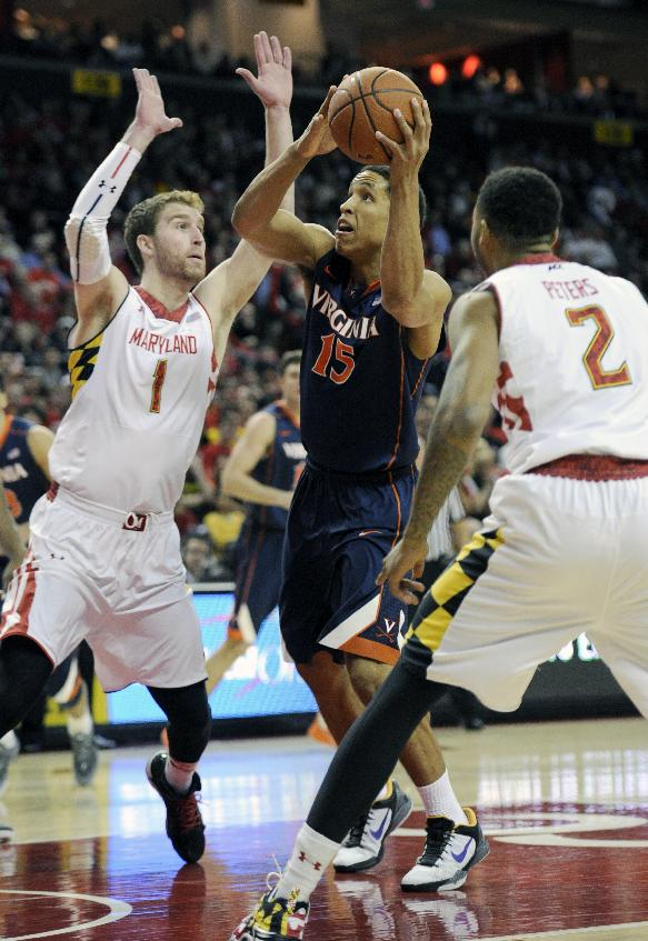 Virginia guard Malcolm Brogdon (15) goes to the basket against Maryland forward Evan Smotrycz (1) and Roddy Peters (2) during the first half of an NCAA college basketball game, Sunday, March 9, 2014, in College Park, Md