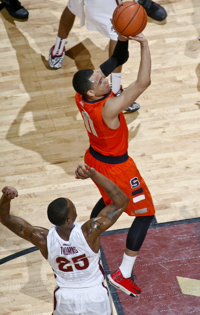 Syracuse guard Tyler Ennis (11), who had 16 points, shoots by Florida State guard Aaron Thomas (25) in the first half of an NCAA college basketball game Sunday, March 9, 2014, at the Donald L. Tucker Center in Tallahassee, Fla. Syracuse defeated Florida State 74-58