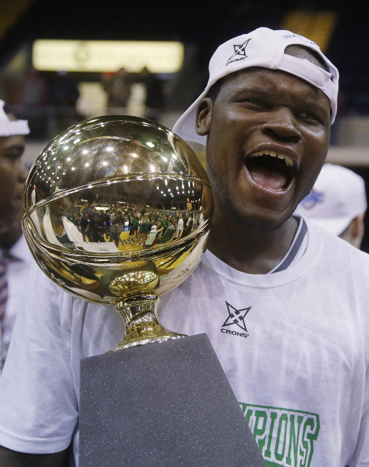 Manhattan forward Rhamel Brown (5) celebrates with the trophy after their NCAA men's MAAC conference championship tournament basketball finals game win over Iona in Springfield, Mass., Monday, March 10, 2014. Manhattan defeated Iona 71-68
