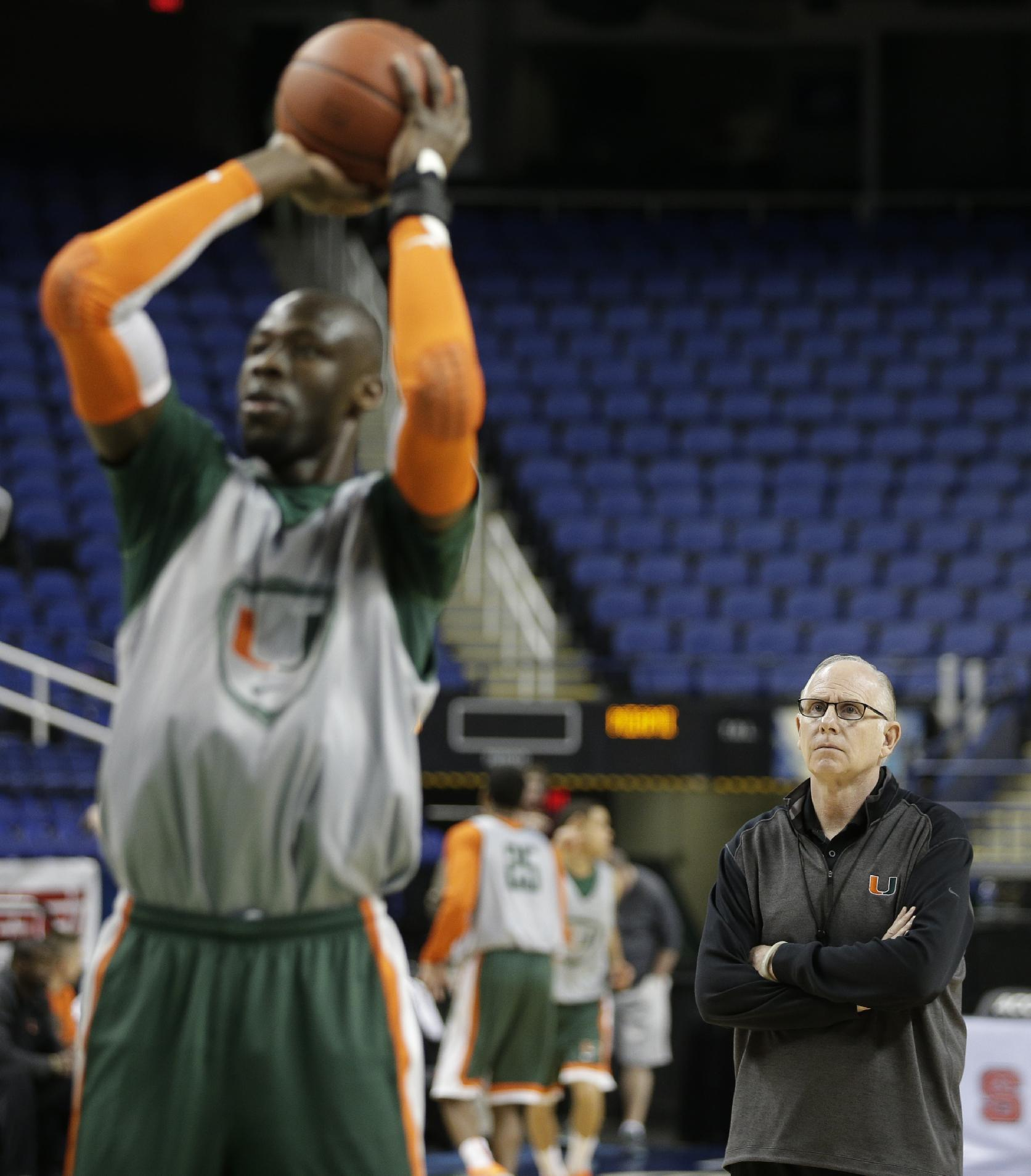 Miami head coach Jim Larranaga, right, watches as Tonye Jekiri , left, takes a shot during an NCAA college basketball practice at the Atlantic Coast Conference tournament in Greensboro, N.C., Tuesday, March 11, 2014. Miami plays against Virginia Tech in a first round game on Wednesday