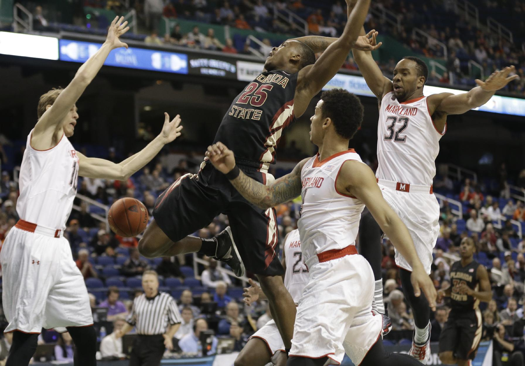 Florida State's Aaron Thomas (25) is fouled as he drives between Maryland's Dez Wells (32), Jake Layman (10), and Seth Allen (4) during the first half of a second round NCAA college basketball game at the Atlantic Coast Conference tournament in Greensboro, N.C., Thursday, March 13, 2014