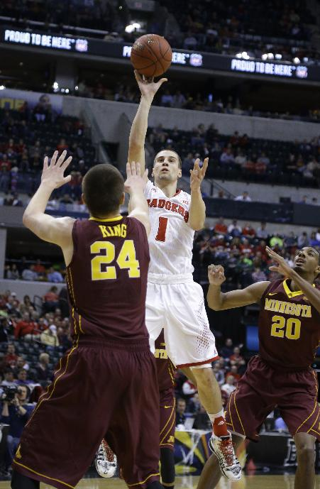 Wisconsin guard Ben Brust (1) shoot over Minnesota forward Joey King (24) as Michigan guard Sean Lonergan (20) watches in the first half of an NCAA college basketball game in the quarterfinals of the Big Ten Conference tournament Friday, March 14, 2014, in Indianapolis