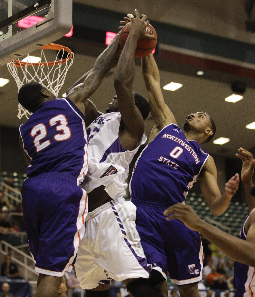 Stephen F. Austin forward Sharife Sergeant (32) is fouled by Northwestern's Zikiteran Woodley (23) while Trav'on Jospeh (0) assists on the play during the second half of an NCAA college basketball game in the semifinal round of the Southland Conference tournament Friday, March 14, 2014, in Katy