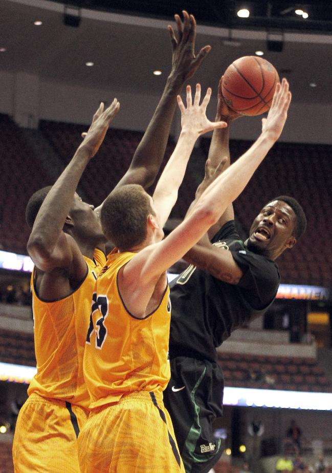 Cal Poly guard Dave Nwaba, right, passes the ball away from UC Irvine center Mamadou Ndiaye, left, and forward Mike Best during the first half of an NCAA college basketball game of the Big West Conference men's tournament in Anaheim, Calif., Friday, March 14, 2014