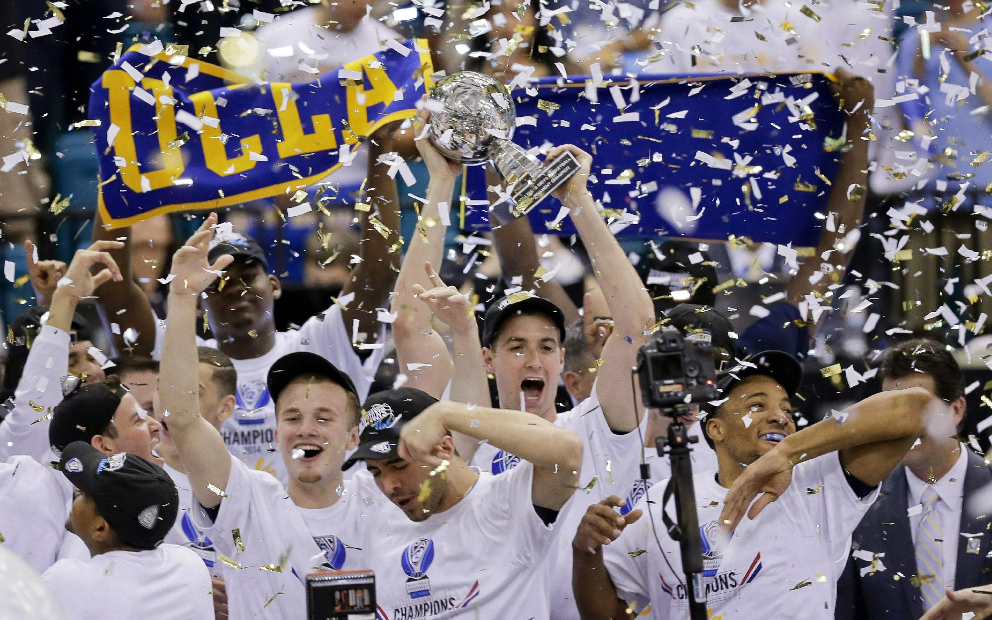 UCLA players celebrate with the championship trophy after beating Arizona 75-71 in the championship game of the NCAA Pac-12 conference college basketball tournament, Saturday, March 15, 2014, in Las Vegas