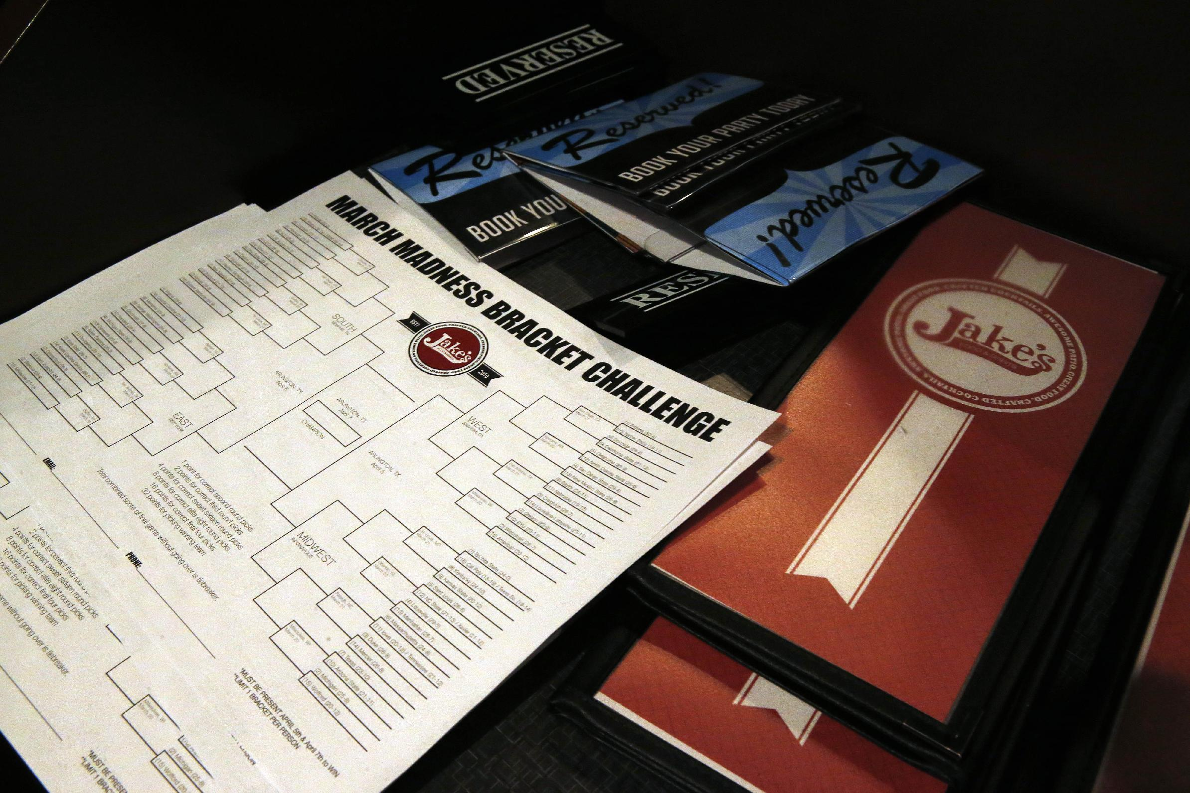 A stack of blank NCAA brackets sits with menus, available to patrons at Jake's sports bar, in Denver, Monday March 17, 2014. Warren Buffett has promised a billion dollars for a perfect NCAA bracket, the chances of which are astronomically small. The NCAA March Madness tournament is to begin Tuesday