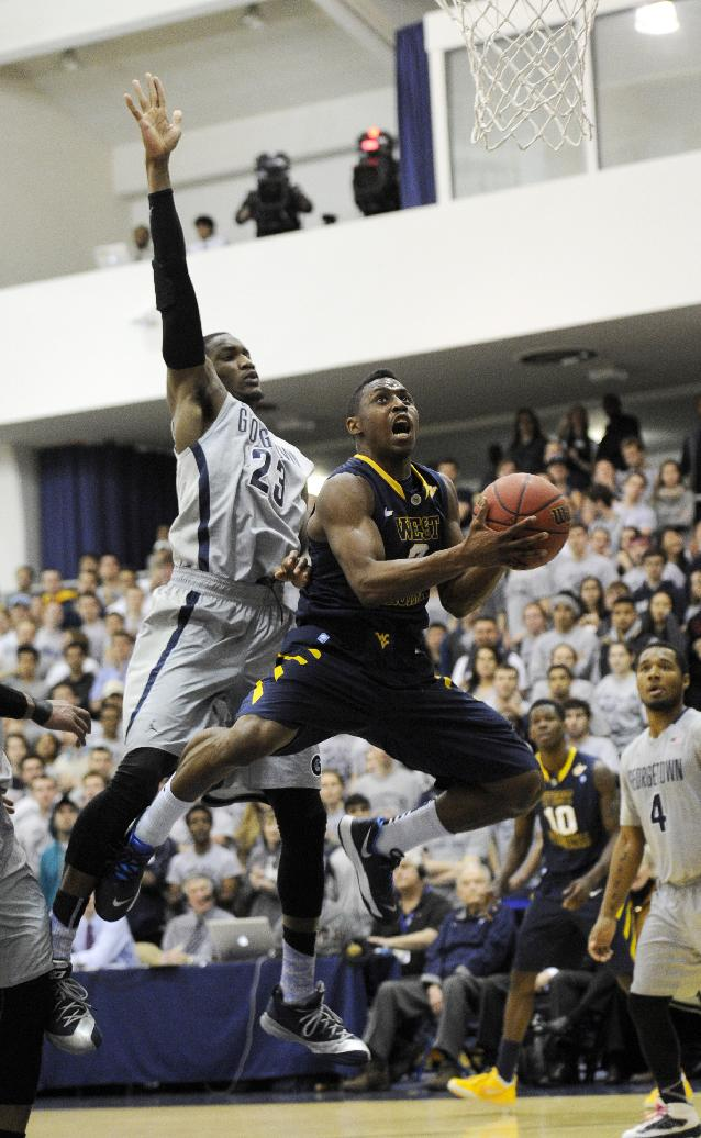 West Virginia guard Juwan Staten, right, goes to the basket against Georgetown forward Aaron Bowen (23) during the first half of an NCAA college NIT tournament first round basketball game, Tuesday, March 18, 2014, in Washington
