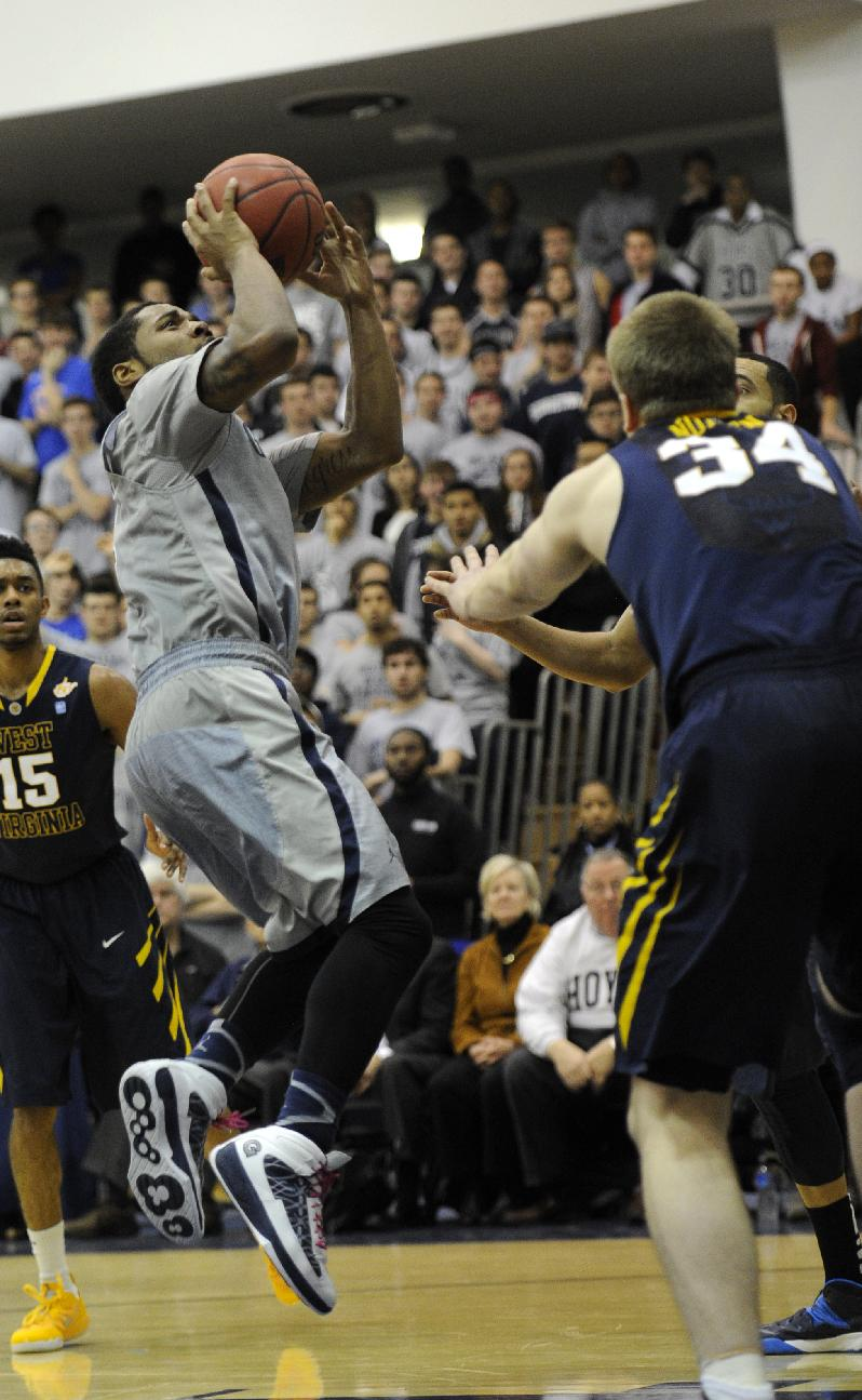 2Georgetown guard D'Vauntes Smith-Rivera, left, takes a shot against West Virginia forward Kevin Noreen (34) during the second half of an NCAA college NIT tournament first round basketball game, Tuesday, March 18, 2014, in Washington. Georgetown won 77-65