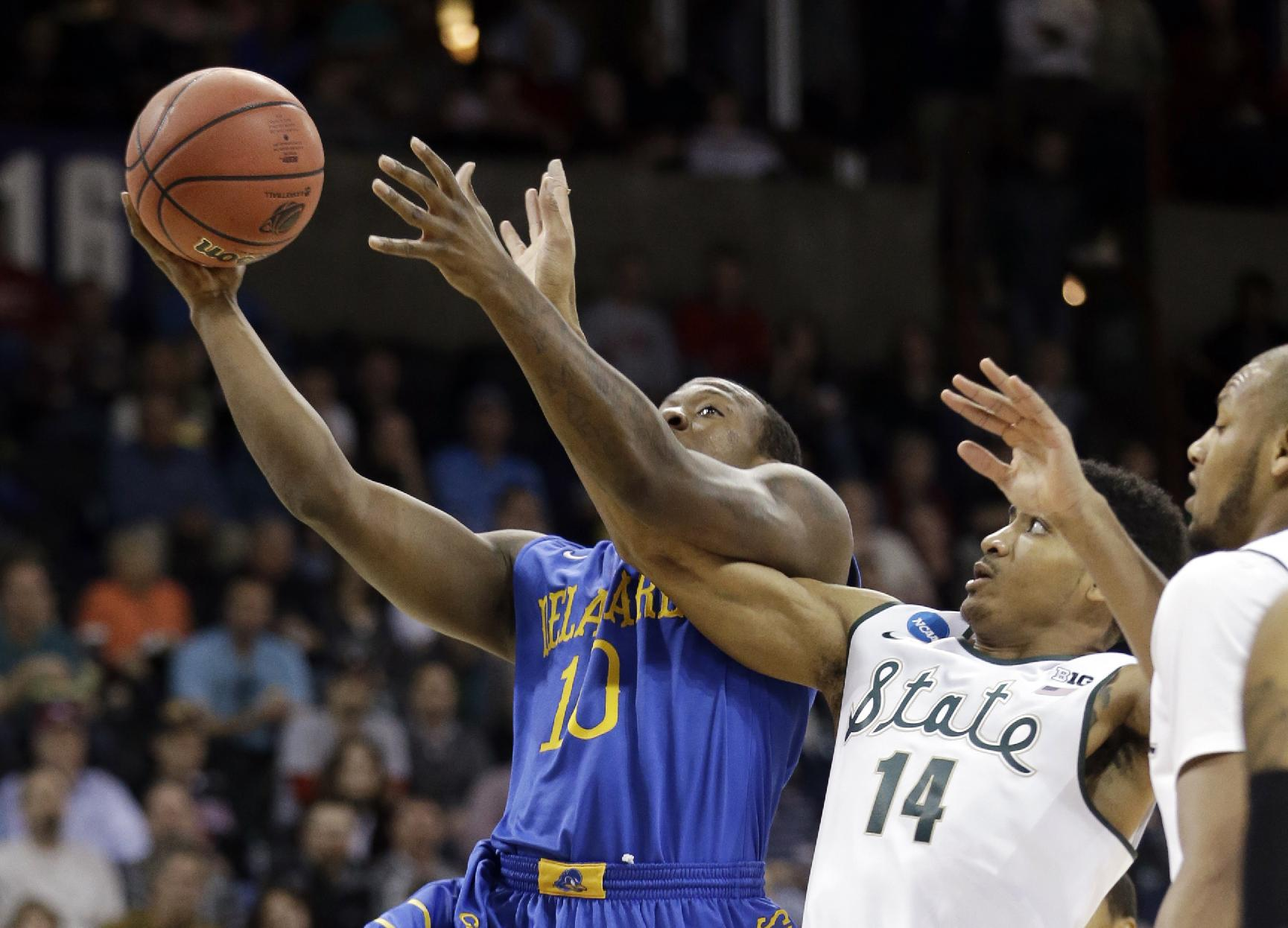 Michigan State's Gary Harris (14) tangles with Delaware's Devon Saddler  during the first half in the second round of the NCAA college basketball tournament in Spokane, Wash., Thursday, March 20, 2014