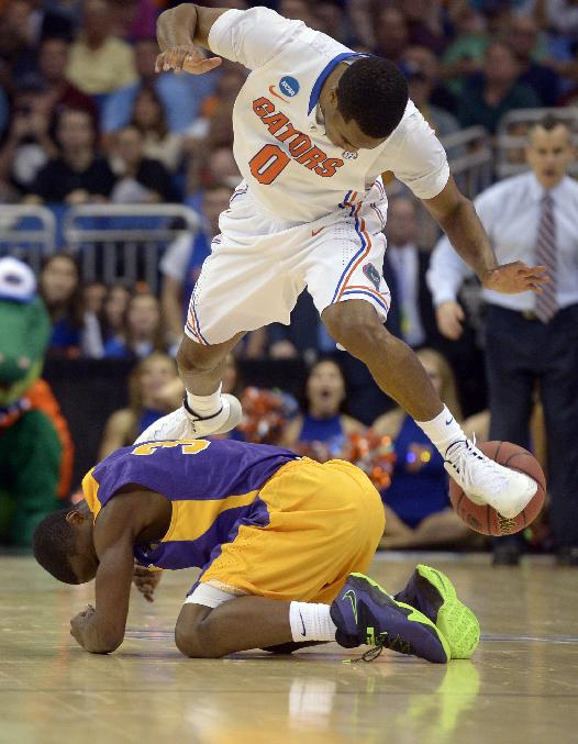 Florida guard Kasey Hill (0) and Albany guard DJ Evans (3) collide after chasing a loose ball during the second half in a second-round game in the NCAA college basketball tournament Thursday, March 20, 2014, in Orlando, Fla. Florida won 67-55