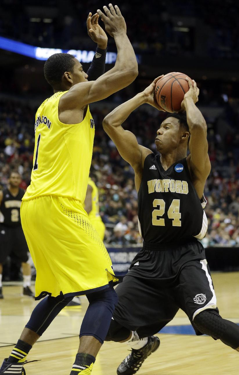 Wofford forward Justin Gordon (24) drives to the basket against Michigan forward Glenn Robinson III (1) during the second half of a second round NCAA college basketball tournament game Thursday, March 20, 2014, in Milwaukee