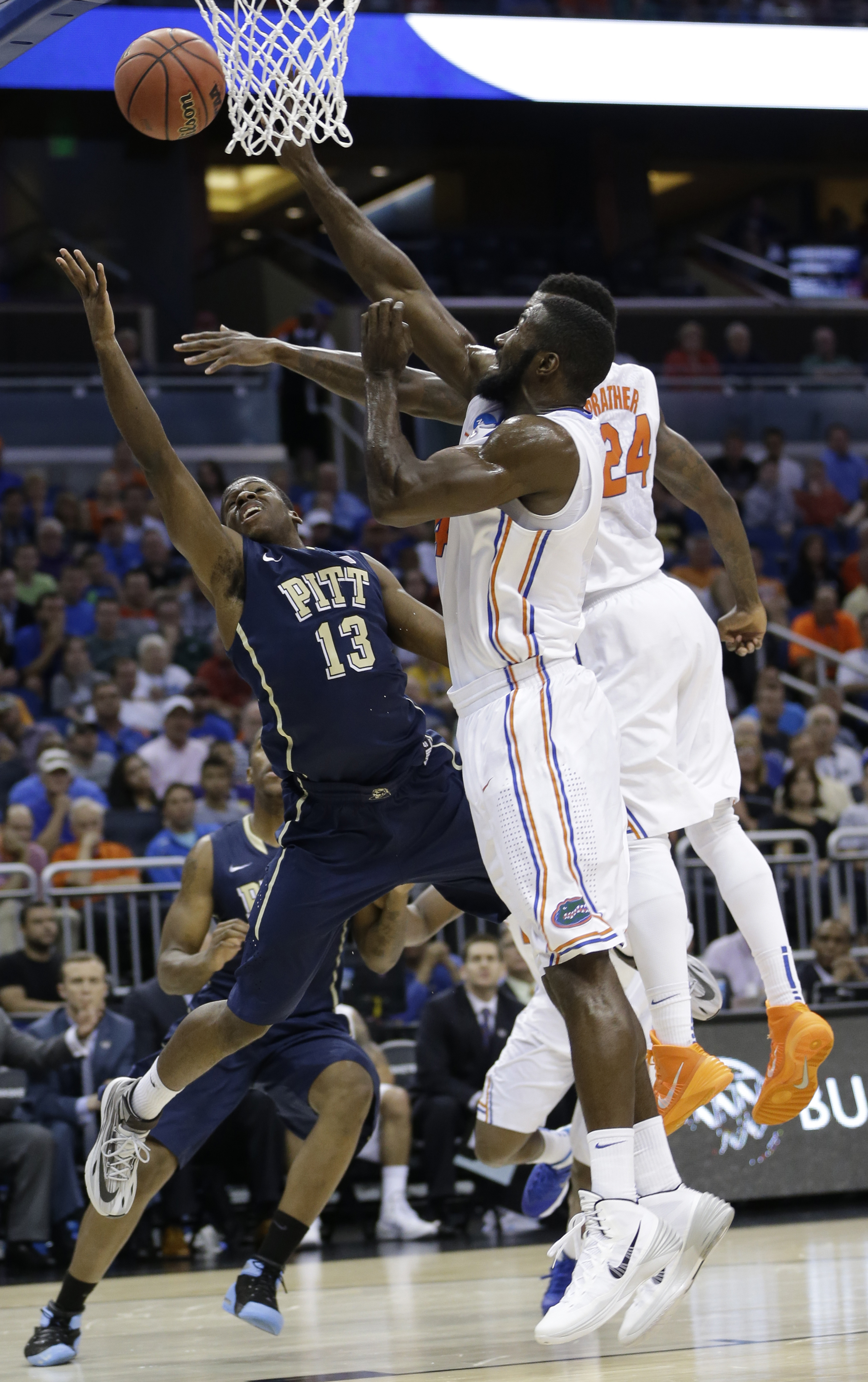 Florida center Patric Young (4) and forward Casey Prather (24) block a shot by Pittsburgh guard Josh Newkirk (13) during the first half in a third-round game in the NCAA college basketball tournament  Saturday, March 22, 2014, in Orlando, Fla