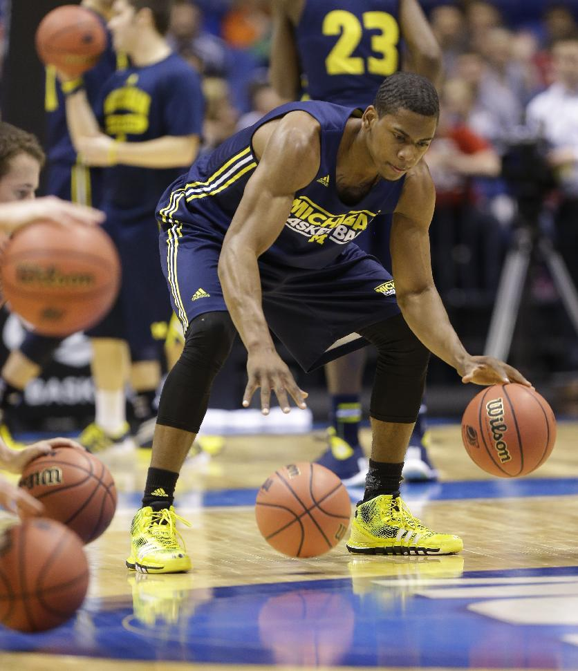 Michigan's Glenn Robinson III dribbles during practice for their NCAA Midwest Regional semifinal college basketball tournament game Thursday, March 27, 2014, in Indianapolis. Michigan plays Tennessee on Friday, March 28, 2013