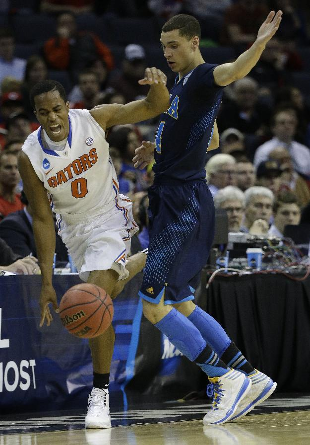 Florida Kasey Hill works against UCLA guard Zach LaVine (14) during the first half in a regional semifinal game at the NCAA college basketball tournament, Thursday, March 27, 2014, in Memphis, Tenn