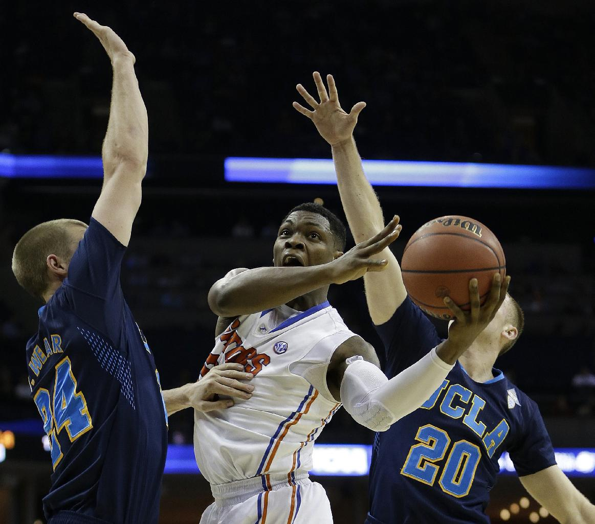Florida guard Michael Frazier II (20) shoots against UCLA's Travis Wear (24) and Bryce Alford (20) during the first half in a regional semifinal game at the NCAA college basketball tournament, Thursday, March 27, 2014, in Memphis, Tenn