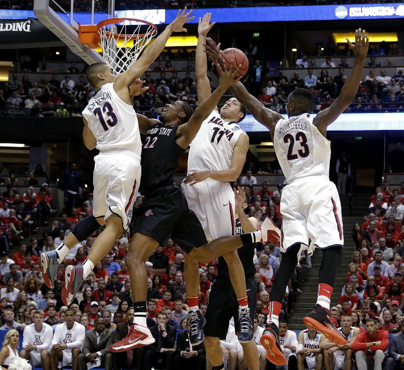 San Diego State forward Josh Davis (22) shoots between Arizona guard Nick Johnson (13), Aaron Gordon (11) and Rondae Hollis-Jefferson (23) during the first half in a regional semifinal of the NCAA men's college basketball tournament, Thursday, March 27, 2014, in Anaheim, Calif