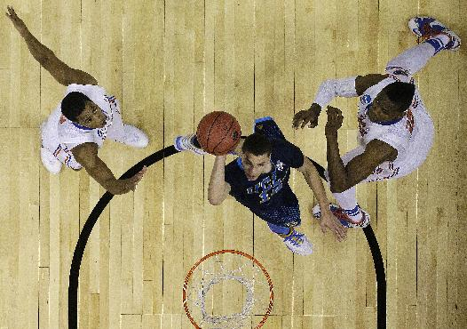 UCLA guard Zach LaVine (14) shoots against Florida forward Will Yeguete, right and Florida Kasey Hill during the first half in a regional semifinal game at the NCAA college basketball tournament, Thursday, March 27, 2014, in Memphis, Tenn