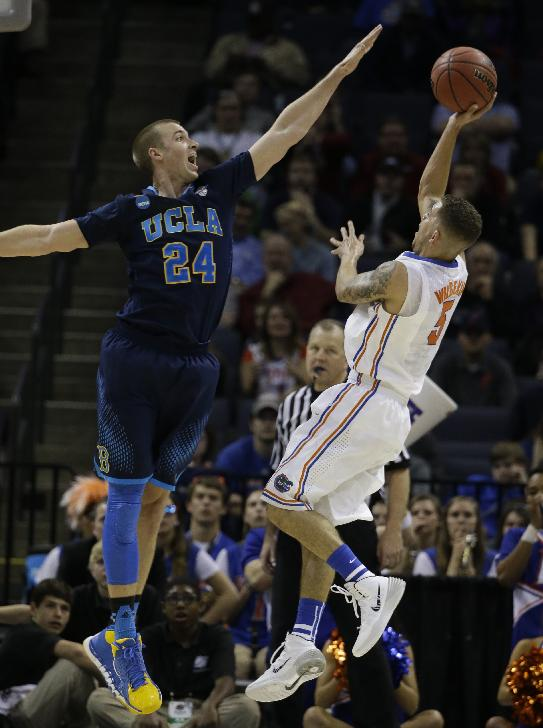 Florida guard Scottie Wilbekin (5) shoots against UCLA forward Travis Wear (24) during the second half in a regional semifinal game at the NCAA college basketball tournament, Thursday, March 27, 2014, in Memphis, Tenn. Florida won 79-68