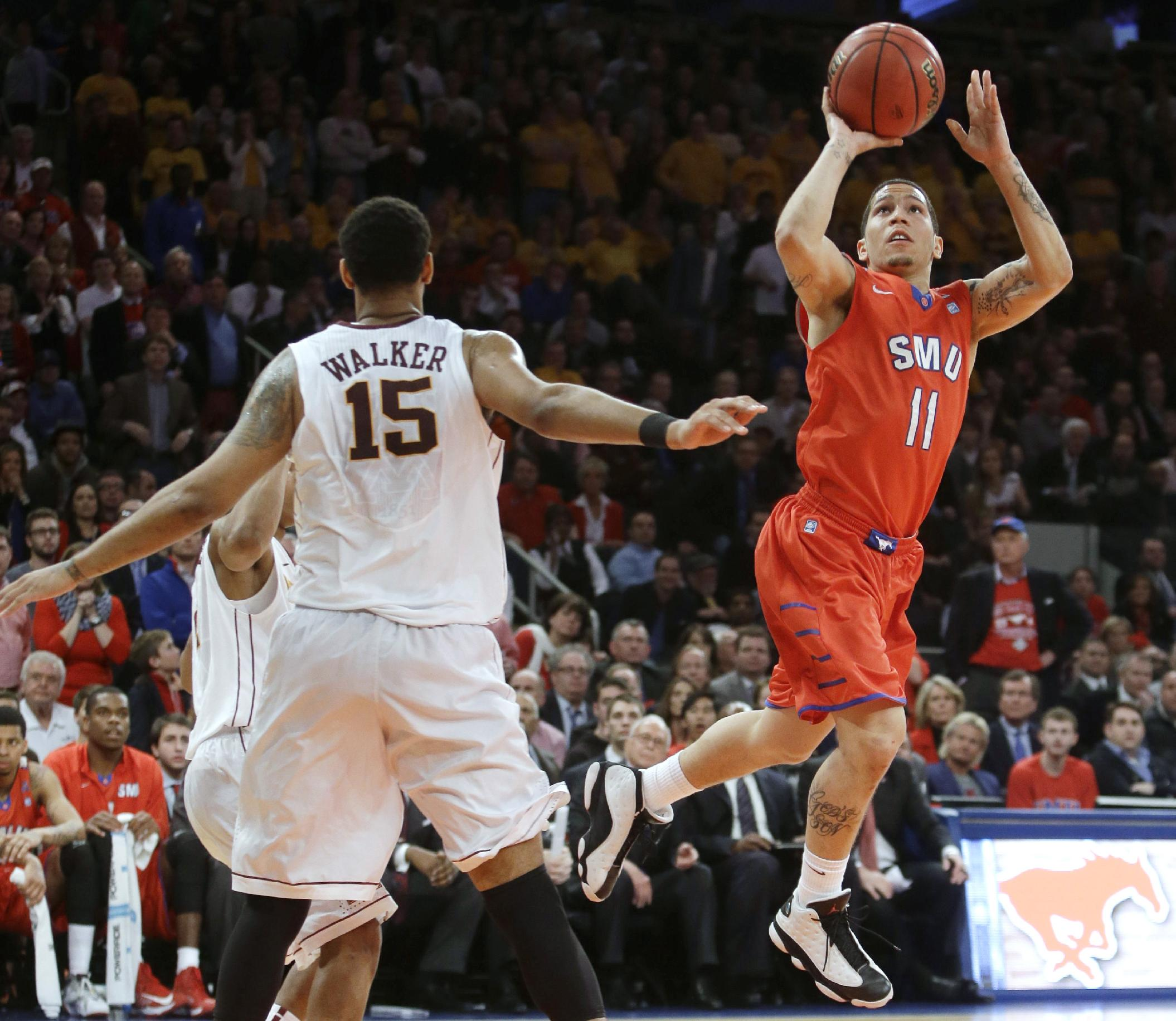 SMU's Nic Moore (11) drives past Minnesota's Maurice Walker (15) during the second half of an NCAA college basketball game in the final of the NIT on Thursday, April 3, 2014, in New York. Minnesota won 65-63