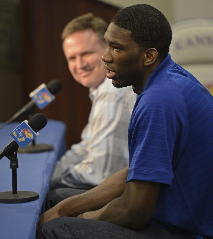 Seated alongside Kansas head coach Bill Self, left, centerJoel Embiid, right, announces his intention to enter the NBA basketball draft in Lawrence, Kan., Wednesday, April 9, 2014