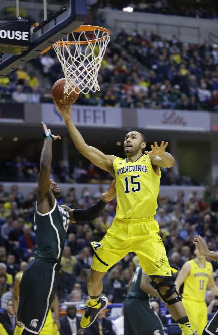 Michigan forward Jon Horford takes a shot against Michigan State guard/forward Branden Dawson in the second half of an NCAA college basketball game in the championship of the Big Ten Conference tournament Sunday, March 16, 2014, in Indianapolis