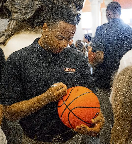 Connecticut's NCAA college basketball player Tor Watts signs an autograph for a fan during Husky Day at the Connecticut Capitol on Wednesday, April 30, 2014, in Hartford, Conn