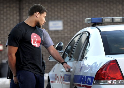 Tyrann Mathieu is placed in a police car at the Baton Rouge Police Department. (AP)