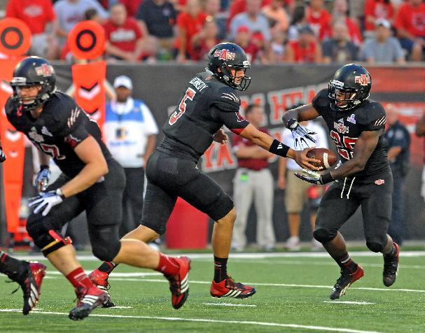 Arkansas State quarterback Adam Kennedy, center, hands the ball to running back David Oku, right, during an NCAA college football game against Troy on Thursday, Sept. 12, 2013, in Jonesboro, Ark. Arkansas State won 41-34