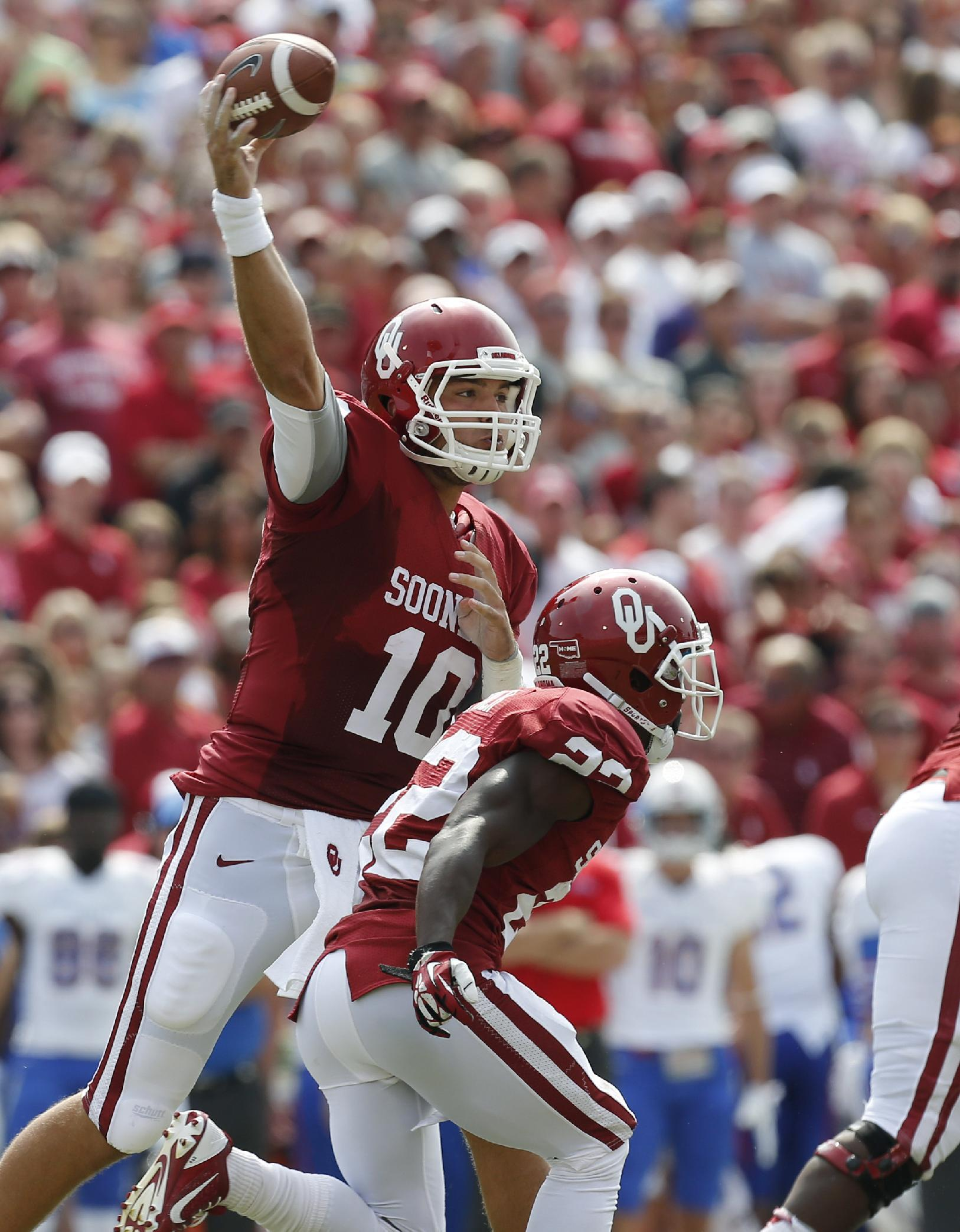 Oklahoma quarterback Blake Bell (10) passes over teammate Roy Finch (22) in the first quarter of an NCAA college football game against Tulsa in Norman, Okla., Saturday, Sept. 14, 2013