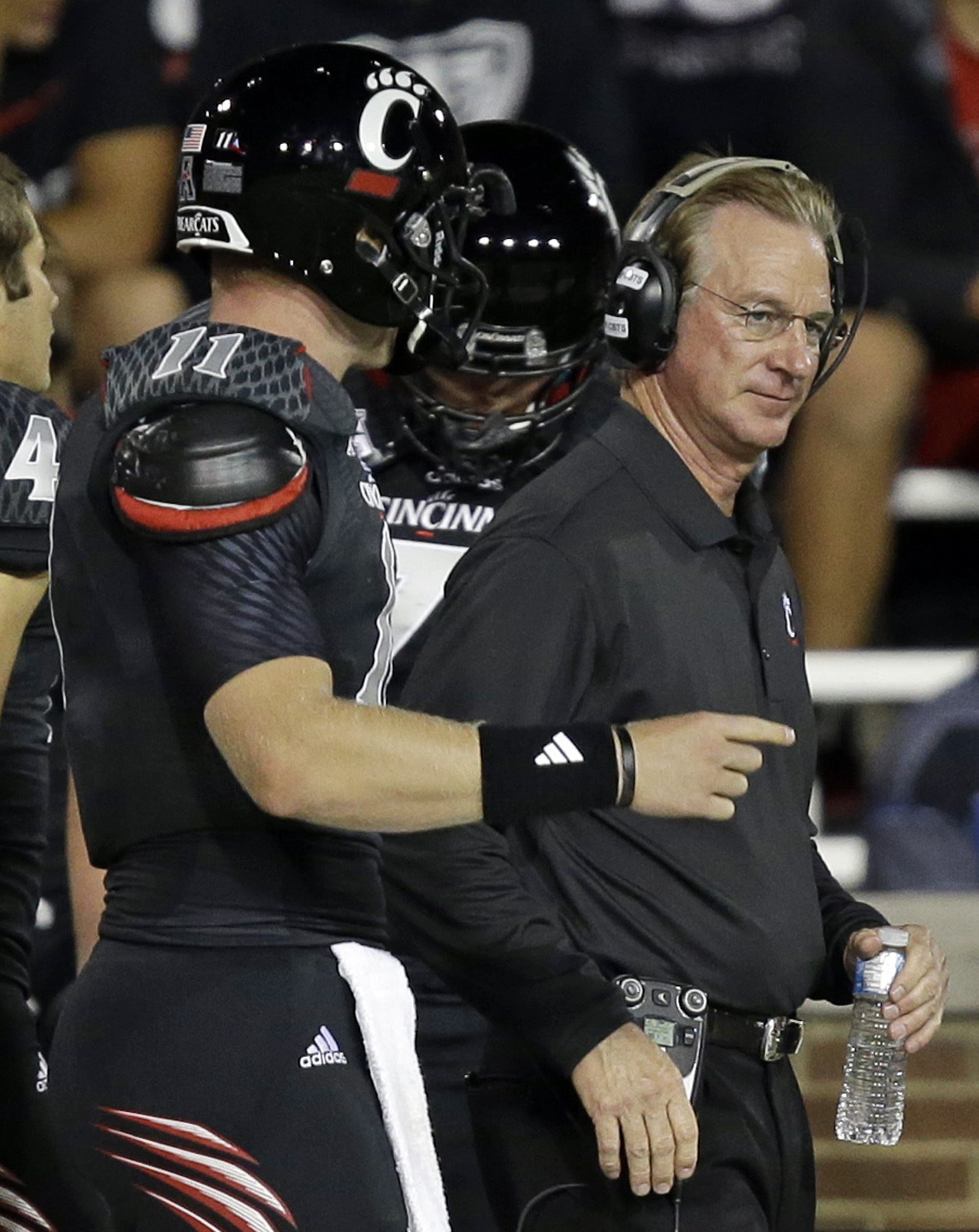 Cincinnati quarterback Brendon Kay, left, talks with head coach Tommy Tuberville in the second half of an NCAA college football game against Northwestern State, Saturday, Sept. 14, 2013, in Cincinnati