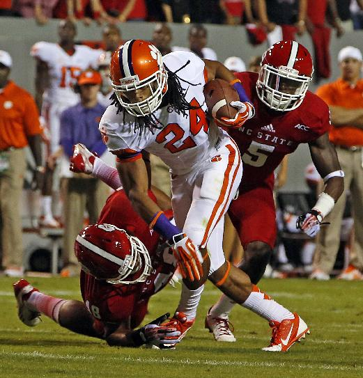 Clemson running back Zac Brooks (24) tries to break away from North Carolina States' Robert Caldwell (48) with  NC State's Rodman Noel (5) nearby during the first half of an NCAA college football game in Raleigh, N.C., Thursday, Sept. 19, 2013