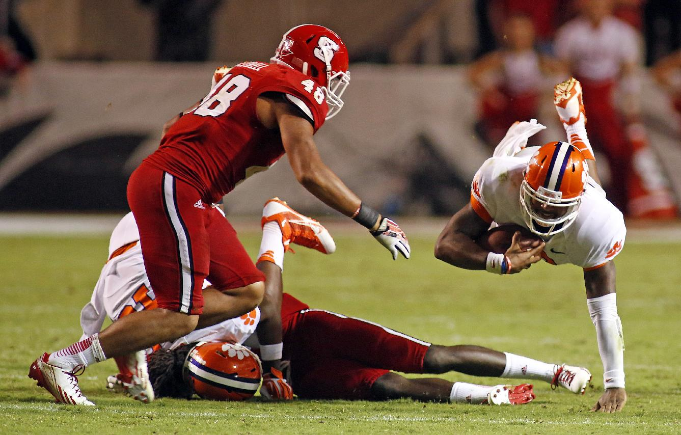 Clemson's Tajh Boyd, right, dives for extra yards with North Carolina State's Robert Caldwell (48) nearby during the second half of an NCAA college football game in Raleigh, N.C., Thursday, Sept. 19, 2013.  Clemson won 26-14