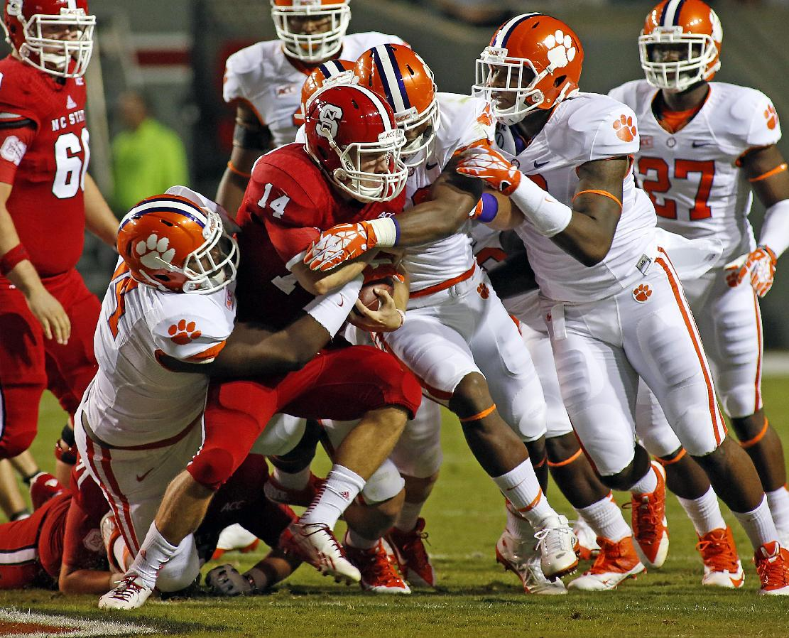 Clemson's Carlos Watkins, left, Stephone Anthony, center, and Corey Crawford tie up North Carolina State's Bryant Shirreffs (14) with Clemson's Robert Smith (27) nearby during the first half of an NCAA college football game in Raleigh, N.C., Thursday, Sept. 19, 2013. Clemson won 26-14