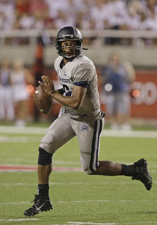 In this Aug. 29, 2013, file photo, Utah State quarterback Chuckie Keeton scambles in the second half of an NCAA football game against Utah in Salt Lake City. By the time Southern California coach Lane Kiffin was done talking this week, the Trojans and their fans were certain Utah State is a BCS title contender and quarterback Chuckie Keeton is a Heisman Trophy front-runner