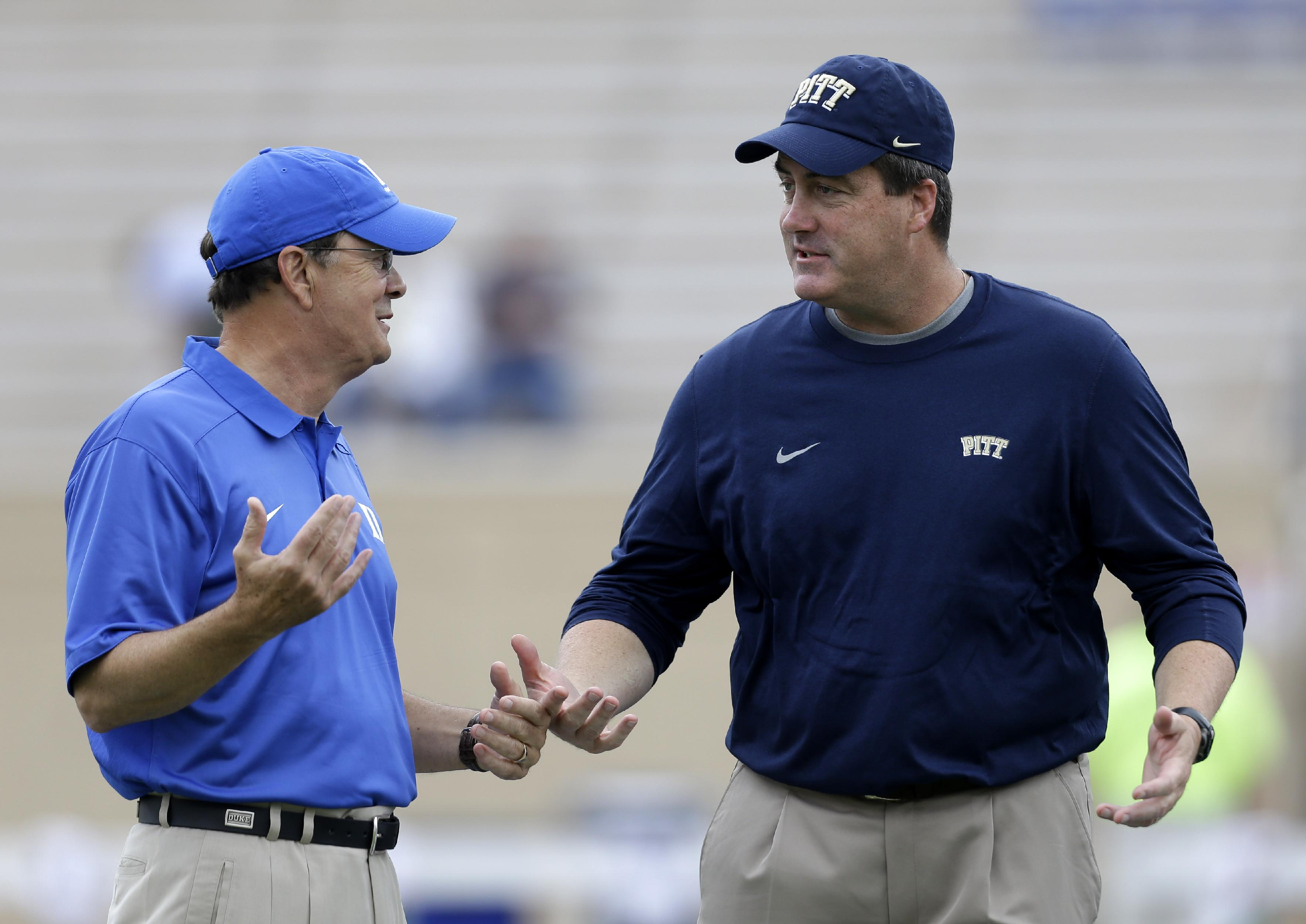 Duke coach David Cutcliffe, left, and Pittsburgh coach Paul Chryst speak prior to an NCAA college football game in Durham, N.C., Saturday, Sept. 21, 2013