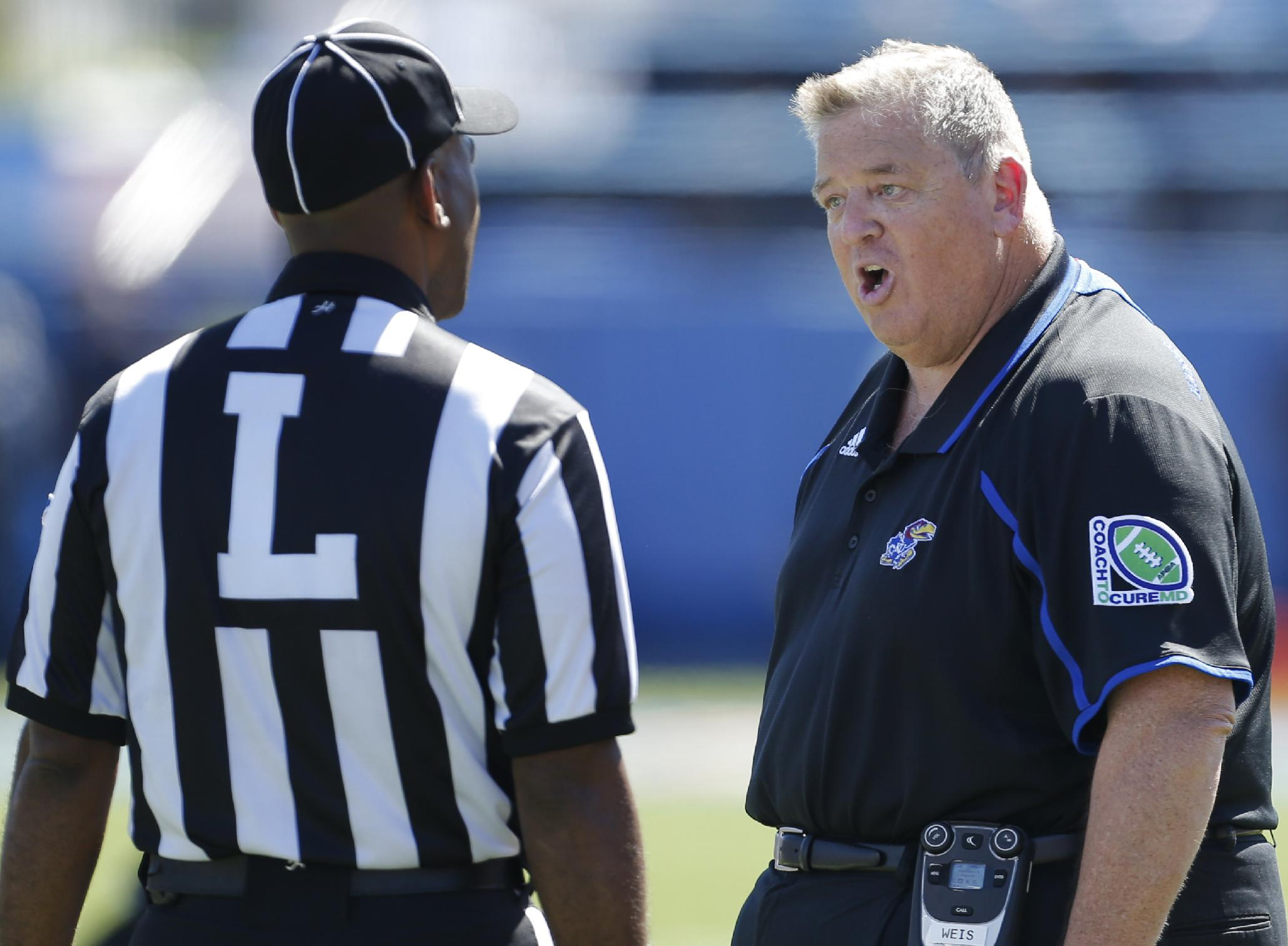 Kansas coach Charlie Weis, right, makes his case with line judge Keith Garmond, left, during the second half of an NCAA college football game against Louisiana Tech in Lawrence, Kan., Saturday, Sept. 21, 2013. Weis wanted a fumble ruled a touchback on the previous play. Kansas defeated Louisiana Tech 13-10