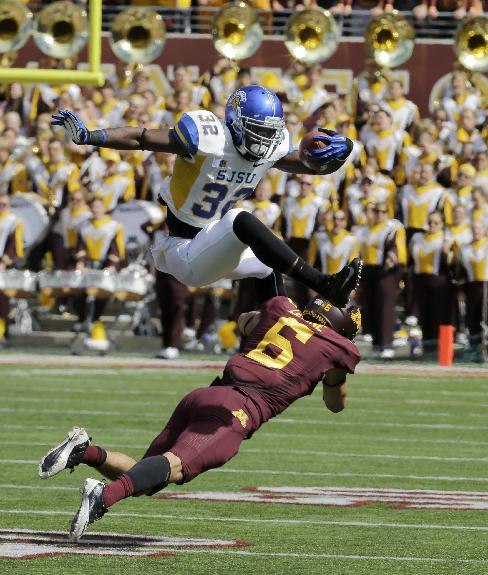 San Jose State running back Jason Simpson (32) leaps over Minnesota defensive back Grayson Levine (6) during the fourth quarter of an NCAA college football game in Minneapolis Saturday, Sept. 21, 2013. The play was called back after San Jose State guard Nicholas Kaspar earned a 15-yard penalty for a chop block. Minnesota beat San Jose State 43-24