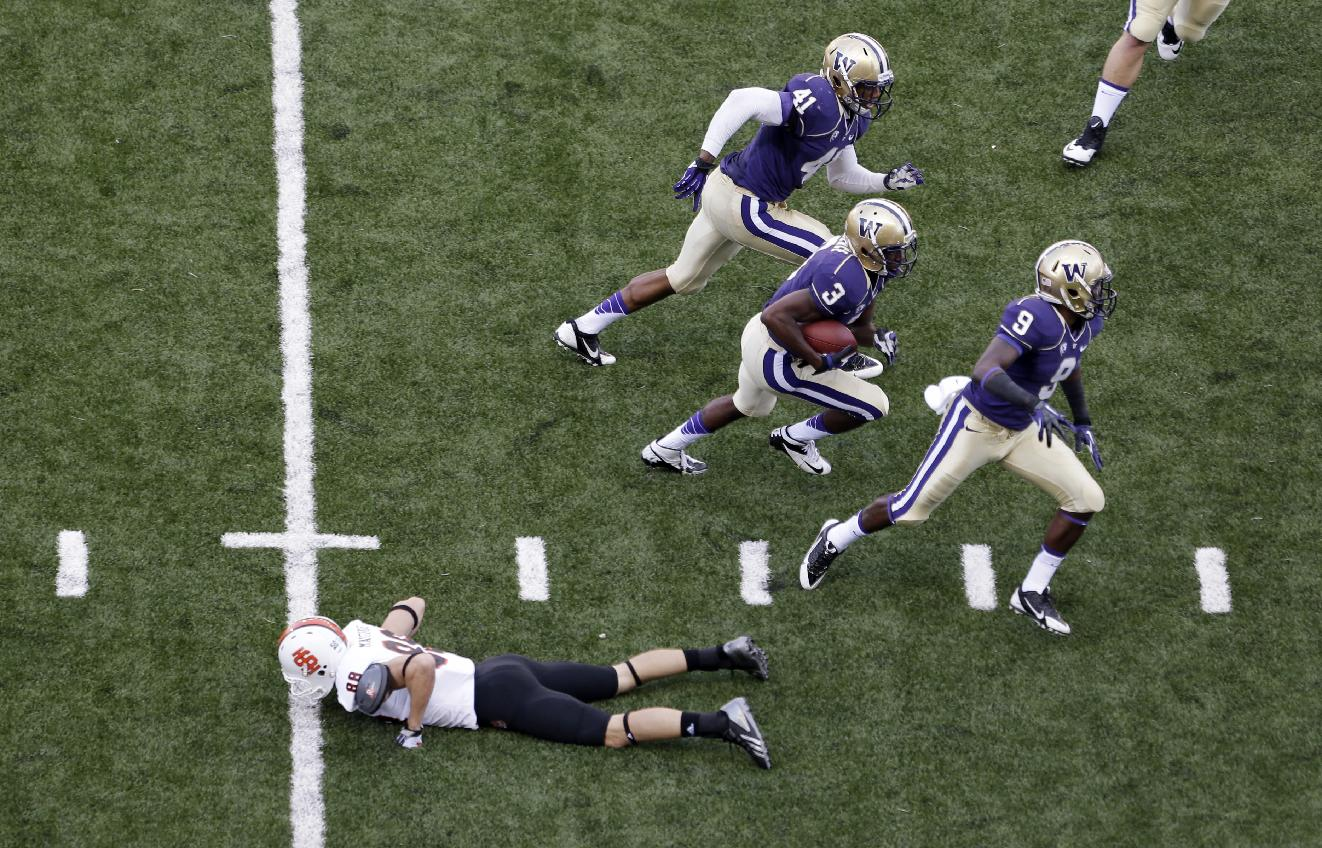 Washington's Cleveland Wallace (3) is flanked by Travis Feeney (41) and Brandon Beaver as he heads upfield after intercepting a pass intended for Idaho State's Madison Mangum in the second half of an NCAA college football game Saturday, Sept. 21, 2013, in Seattle. Washington won 56-0