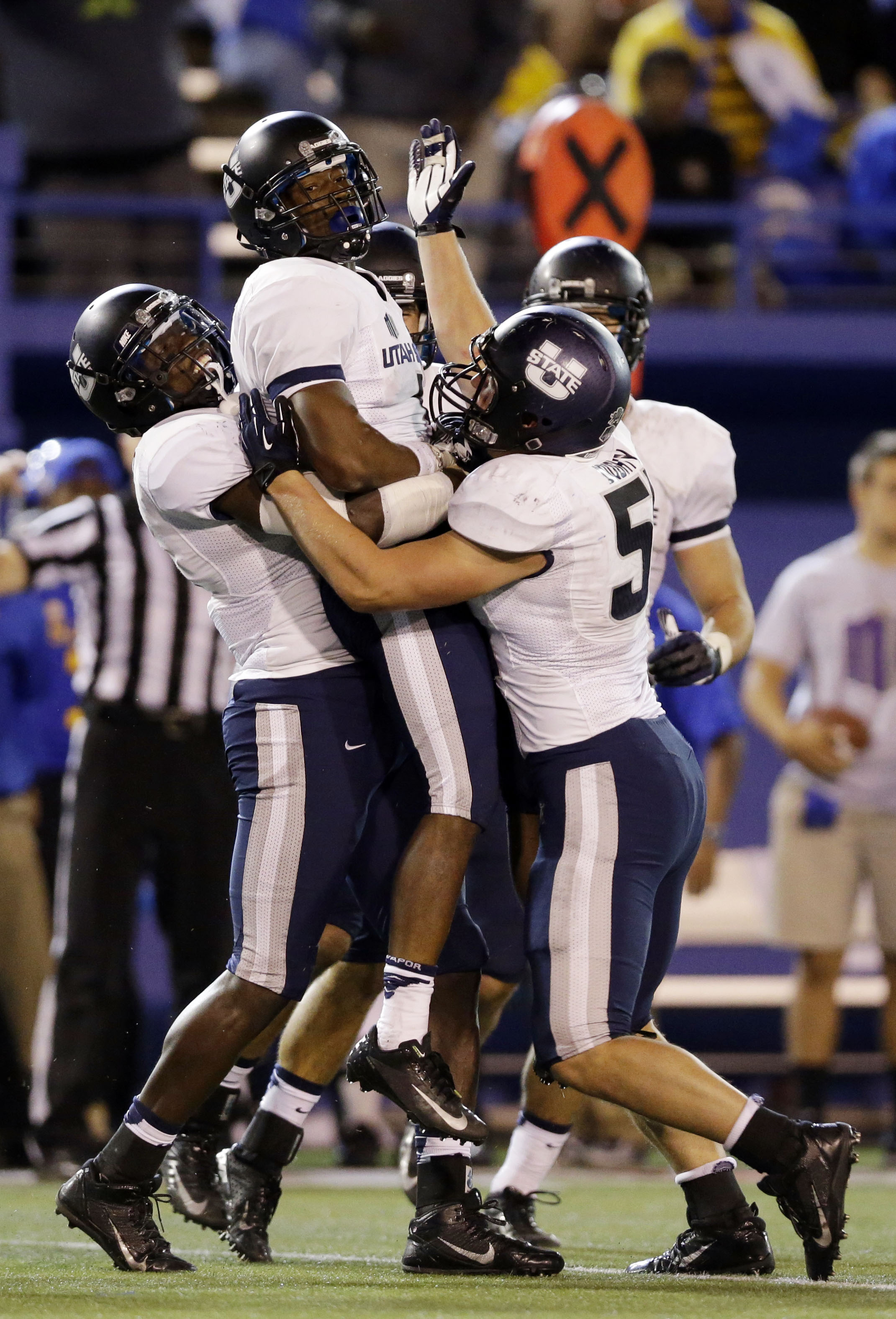 Utah State's Nevin Lawson, center, is lifted by teammates after intercepting a pass against San Jose State during the second half of an NCAA college football game on Friday, Sept. 27, 2013, in San Jose, Calif