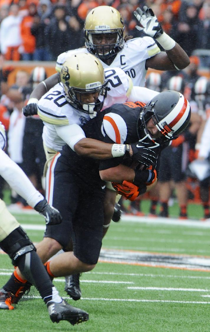 Oregon State's Richard Mullaney is tackled by Colorado's Greg Henderson (20) after a catch in the first half of an NCAA college football game on Saturday, Sept 28, 2013, in Corvallis, Ore