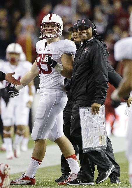 Stanford head coach David Shaw, right, smiles after greeting Devon Cajuste on the sidelines after Cajuste's second touchdown against Washington State in the first half of an NCAA college football game Saturday, Sept. 28, 2013, in Seattle