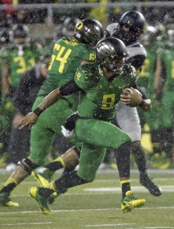 Oregon quarterback Marcus Mariota rushes during the first half of an NCAA college football game against California in Eugene, Ore., Saturday, Sept. 28, 2013